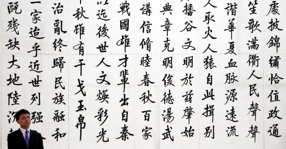 25.mai.2012 - Segurança aguarda nesta sexta-feira (25) em frente a painel com símbolos da caligrafia chinesa durante cerimônia oficial de entrega do prêmio Pritzker de arquitetura, em Pequim, na China