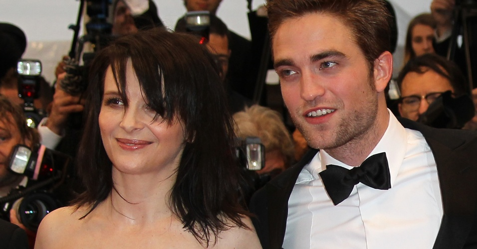 """A atriz francesa Juliette Binoche e o ator britânico Robert Pattinson posam para fotos no tapete vermelho do Palácio do Festival ao chegarem à exbição de """"Cosmopolis"""" no Festival de Cannes 2012. (25/5/12)"""