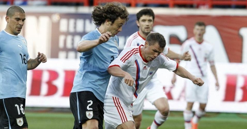 Diego Lugano, do Uruguai, disputa bola com Marat Izmailov em amistoso realizado em Moscou nesta sexta-feira