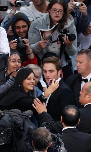 """O ator Robert Pattinson é cercado por fãs ao chegar à exibição do filme """"Cosmopolis"""" no Festival de Cannes 2012 (25/5/12)"""