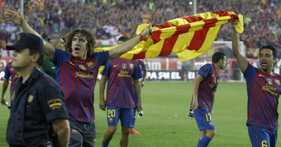 Puyol e Xavi seguram a bandeira da Catalunha durante a volta olímpica após a conquista do título da Copa do Rei