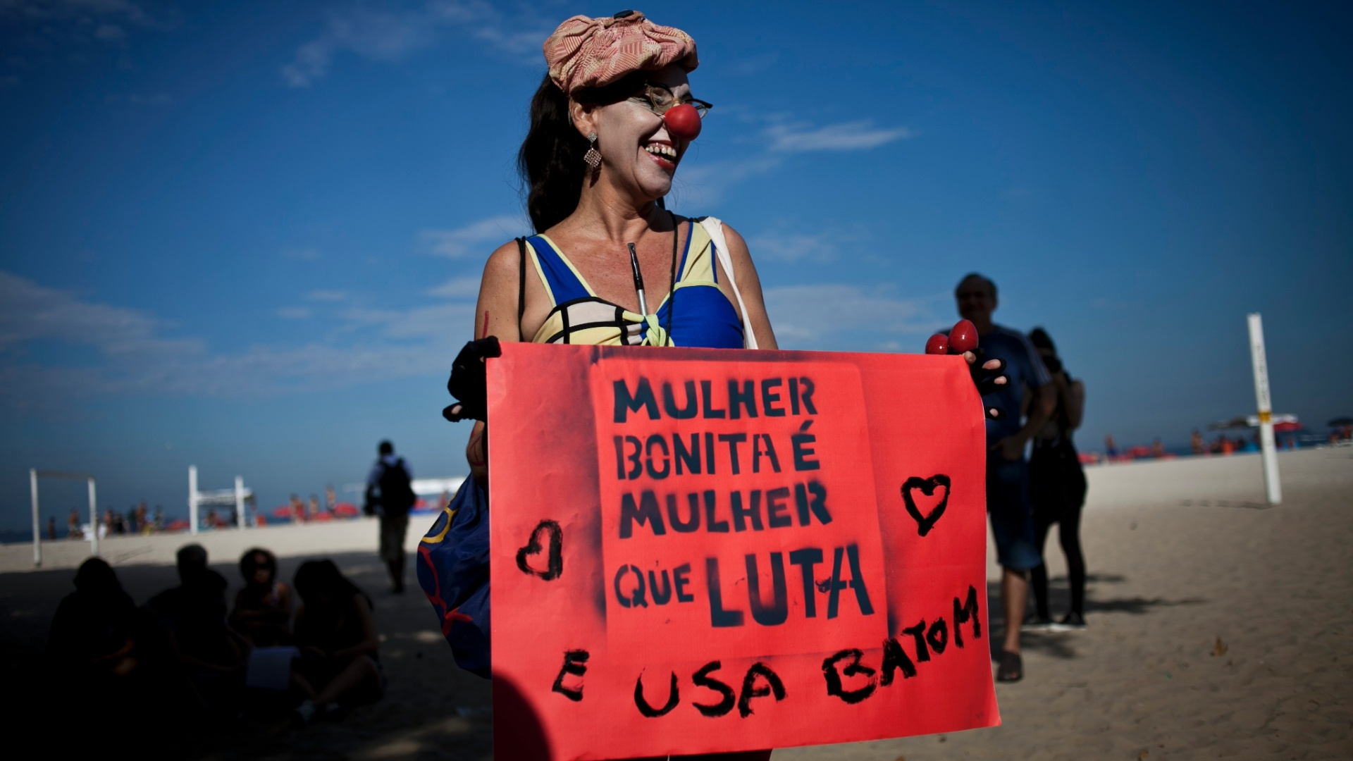 Em dia ensolarado, mulher vai  Marcha das Vadias na Praia de Copacabana