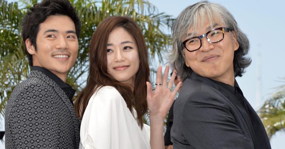 """Kim Kang-woo (à esq) e Kim Hyo-jin (centro) e o diretor Im Sang-soo,passam pelo tapete vermelho antes da exibição do longa """"The Taste of Money"""" no Festival de Cannes, na França (26/5/12)"""