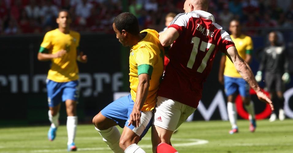 O meia Lucas tenta passar pelo rival dinamarquês em amistoso na Alemanha