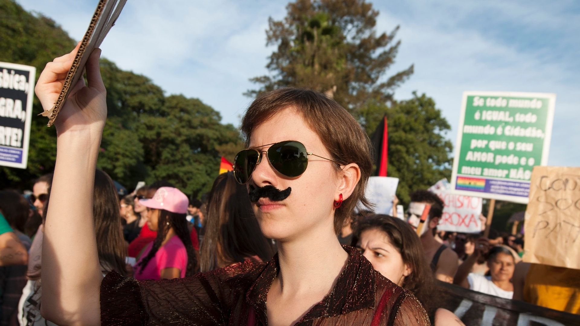 27.05.2012 - De bigode, mulher defende os direitos femininos na Marcha das Vadias em Porto Alegre