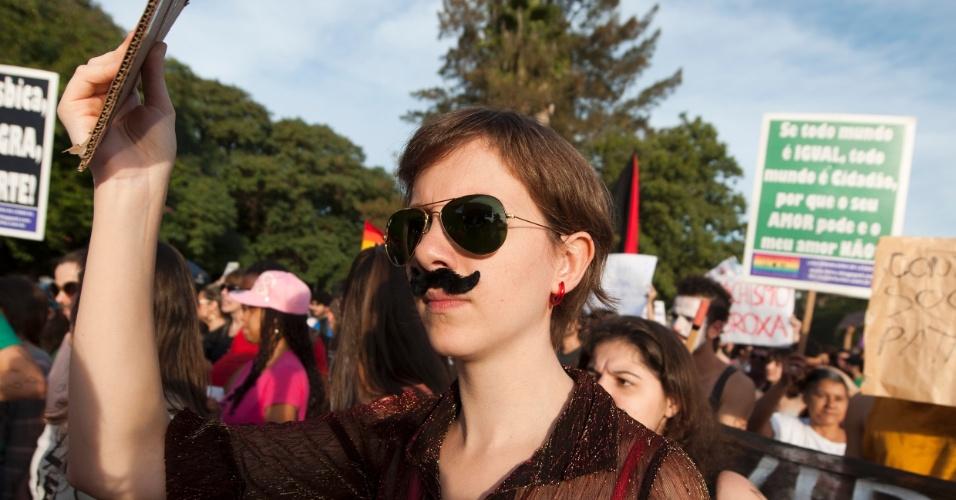 27.05.2012 - De bigode, mulher defende os direitos femininos na Marcha das Vadias em Porto Alegre