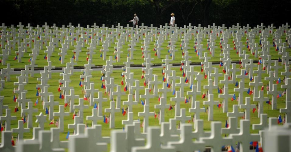 27.mai.2012 - Norte-americanos caminham por túmulos de soldados mortos na Segunda Guerra Mundial (1939 a 1945) quando é celebrado o Dia da Memória Americana, no cemitério Americano, em Manila, nas Filipinas