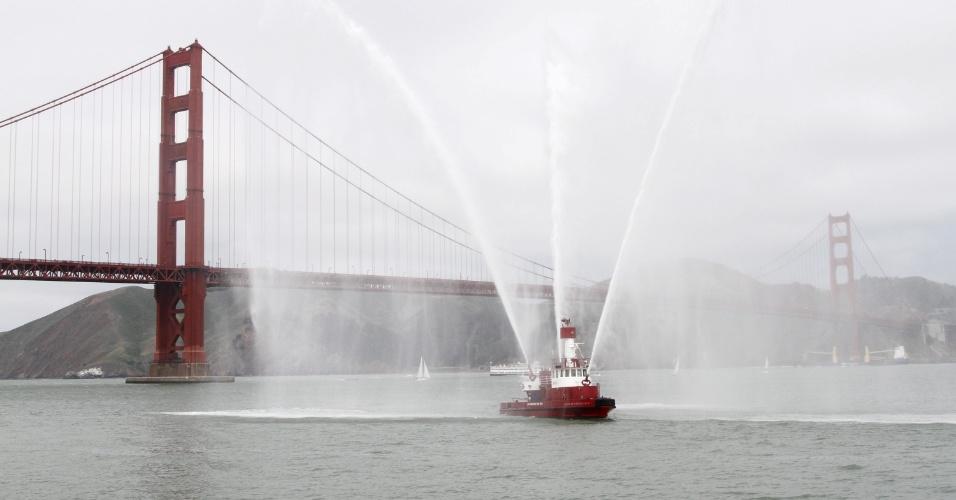 Barco dos bombeiros de São Francisco, nos Estados Unidos, espirra água próximo à Golden Gate na comemoração do aniversário de 75 anos da ponte, neste domingo (27)