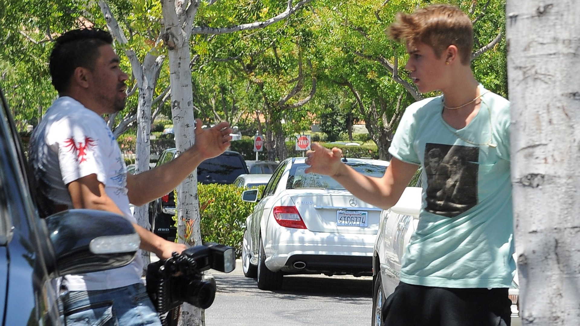 Justin Bieber ( dir.) discute com paparazzo em frente a shopping center de Los Angeles (27/5/12)