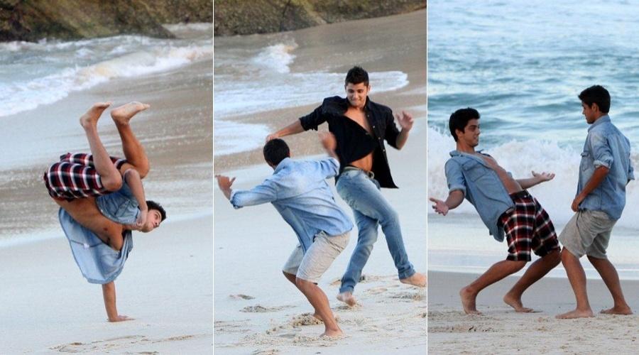Rodrigo Simas e Bruno Gissoni lutam capoeira com o irmão caçula, Felipe, na praia do Arpoador, zona sul do Rio (28/5/12)