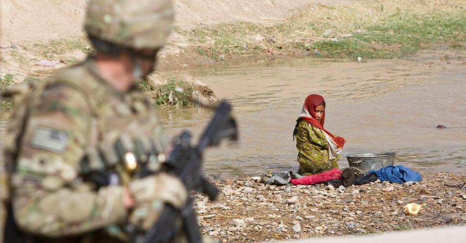 29.mai.2012 - Garota lava roupas em rio nesta terça-feira (29) enquanto soldado do Exército dos Estados Unidos passa por ela na cidade de Senjaray, no Afeganistão