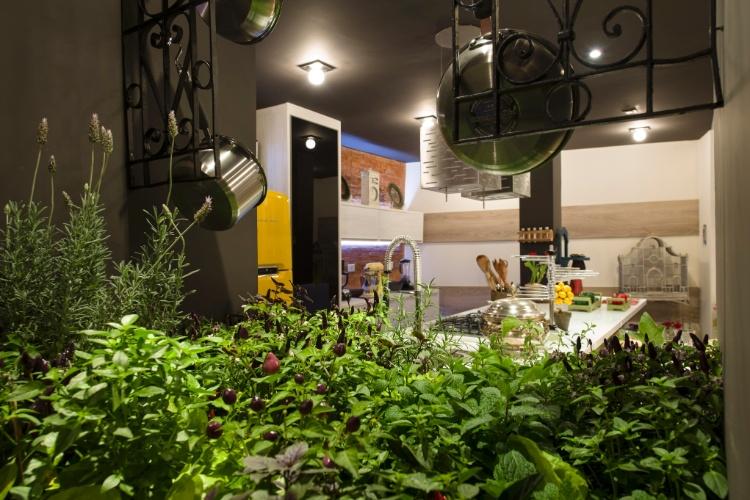 """A Cozinha da Casa de Campo, para a 26ª Casa Cor SP, criada por Claudio Porsé, tem """"cara"""" de casa de vô, com ares antigos, mas sem deixar de lado as facilidades dos mobiliários e equipamentos modernos. A bancada da cozinha, com o fogão e a pia, termina com uma horta de temperos"""