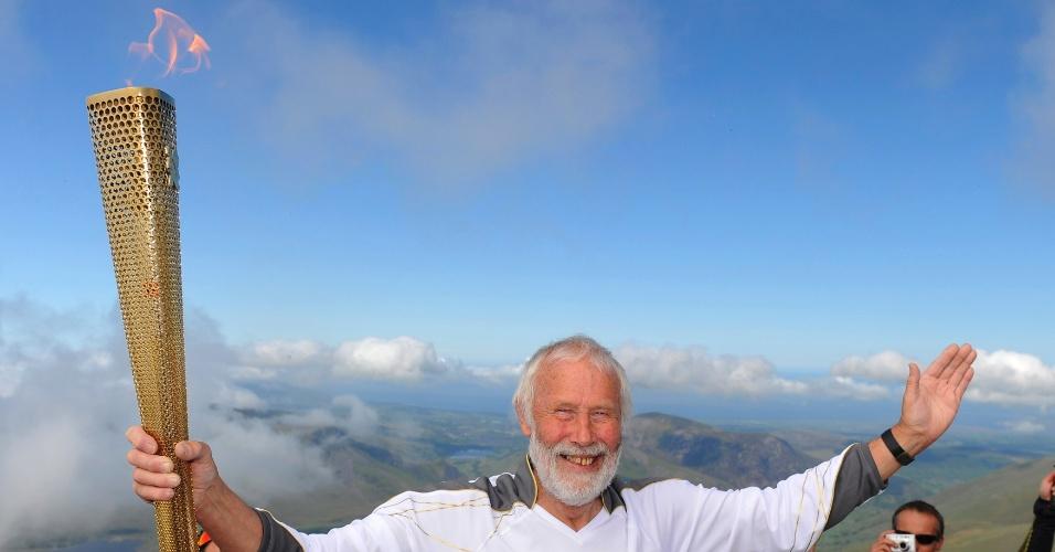 Alpinista inglês Chris Bonnington segura a tocha olímpica no cume do Snowdon, o ponto mais alto do País de Gales