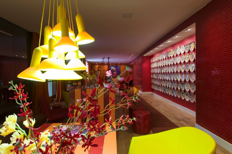 No Living Sabrina Sato, projetado para a Casa Cor SP 2012 pela arquiteta Bunete Fraccaroli, as cores vibrantes se espalham, com destaque para a uma mesa central de 14 m de comprimento, em tons de laranja e vermelho. Na parede lateral à mesa, foram pendurados pratos em cerâmica com ilustrações de caveira