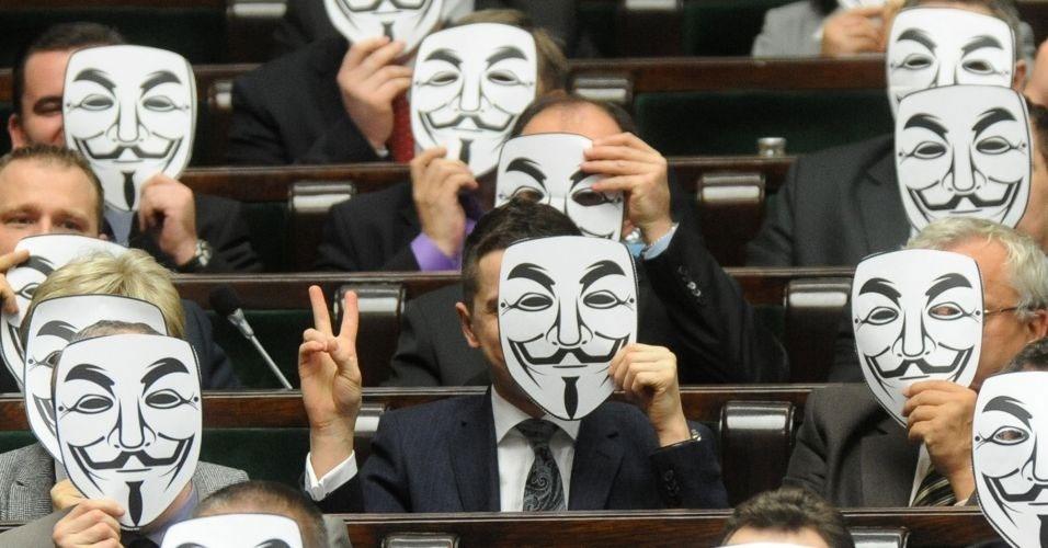 25.jan.2012 - Deputados da esquerda polonesa usam máscaras símbolo do grupo hacker 'Anonymous' para protestar contra a adesão do país a padrões internacionais de direitos autorais (ACTA, na sigla em inglês), durante sessão do Parlamento em Varsóvia. O tratado foi assinado pelo primeiro-ministro do país, Donald Tusk, mesmo contra a opinião pública