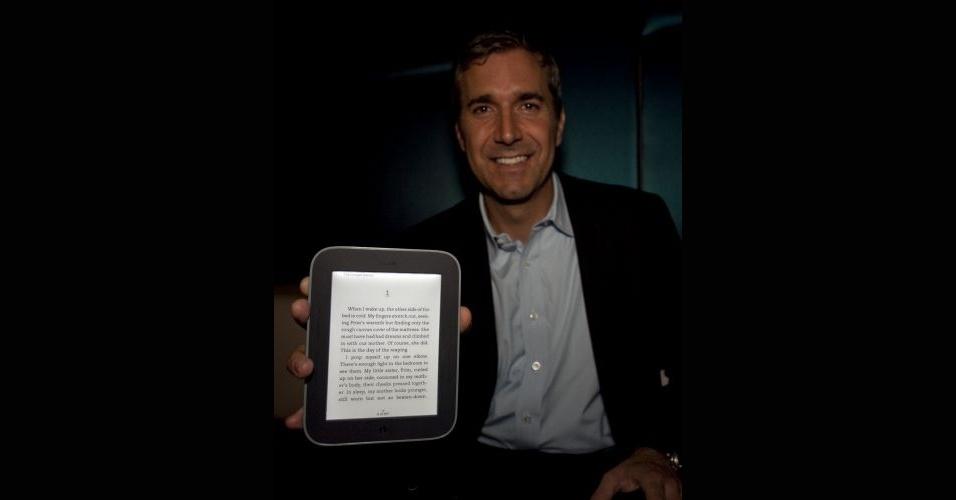 13.abr.2012 - A livraria americana Barnes & Noble apresentou uma nova versão do seu leitor de e-books: o Nook Simple Touch. O aparelho traz como novidade o recurso glow light. Com ele, é possível ler livros na tela e-ink (tinta digital) de 6 polegadas em ambientes escuros, graças a um sistema que erradia levemente uma luz no fundo da tela. Em outros leitores eletrônicos do tipo, só é possível ler em ambientes com boa iluminação, uma vez que a tecnologia e-ink procura emular a leitura em papel. O e-reader está em pré-venda nos Estados Unidos por US$ 139 e estará disponível nas lojas a partir de 1º de maio. Na imagem, William Lynch, CEO da Barnes & Noble, segura o Nook Simple Touch