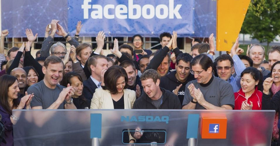 18.maio.2012 - Mark Zuckerberg, CEO do Facebook, toca o sino de abertura da Nasdaq, em Menlo Park, sede da empresa nos EUA), e deixa sua assinatura em placa 