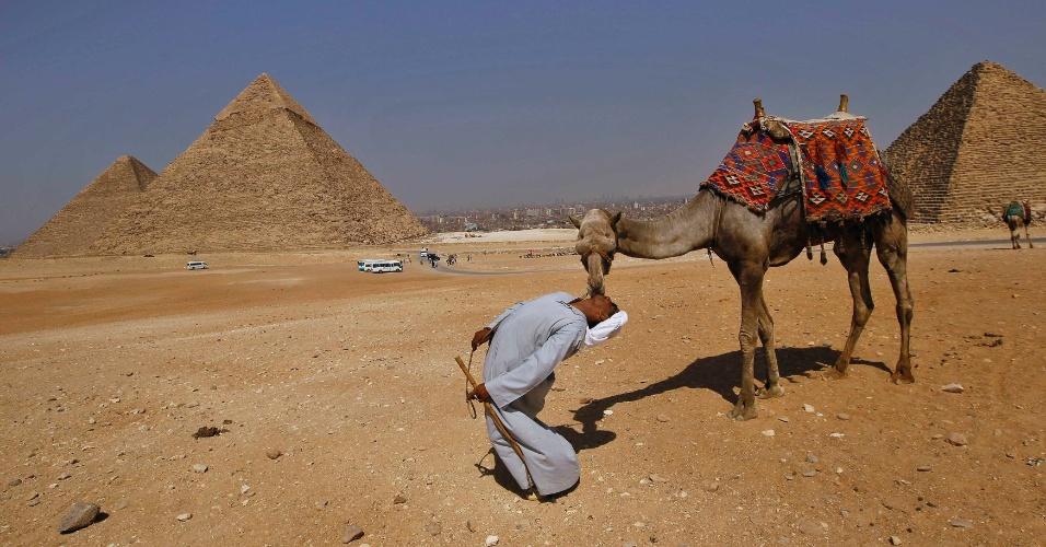 31.mai.2012 - Homem beija camelo na boca nas pirâmides Plateau, em Giza, no Egito