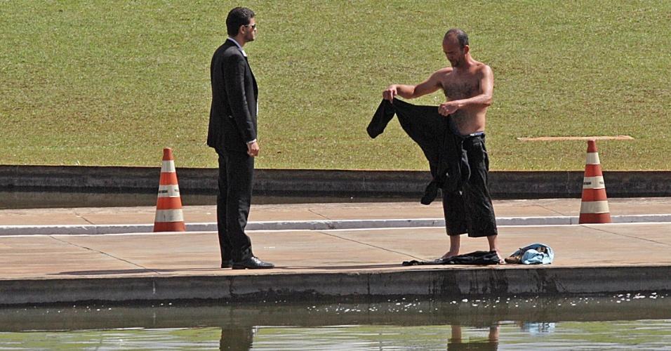 31.mai.2012 - Homem é repreendido por segurança após ser flagrado tomando banho no espelho d'água do Congresso Nacional, em Brasília, nesta quinta-feira (31)