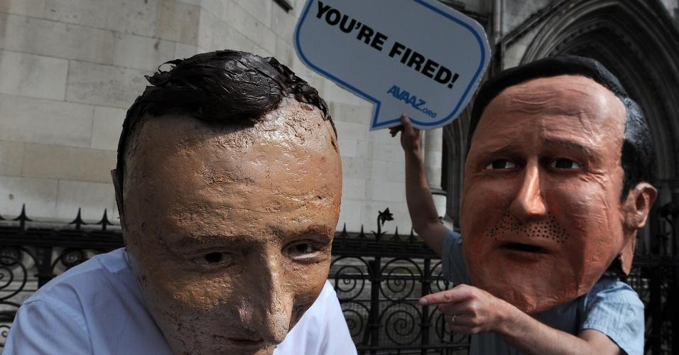 31.mai.2012 - Manifestantes do grupo Avaaz protestam nesta quinta-feira (31) contra o inquérito Leveson,  usando máscaras do primeiro-ministro inglês, David Cameron, (dir.) e do secretário de cultura inglês, Jeremy Hunt (esq.), em frente ao prédio da alta corte de Londres, na Inglaterra