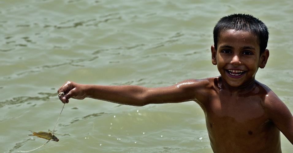 31.mai.2012 - Menino mostra peixe capturado em lagoa de Nova Déli, na Índia, de altas temperaturas na cidade