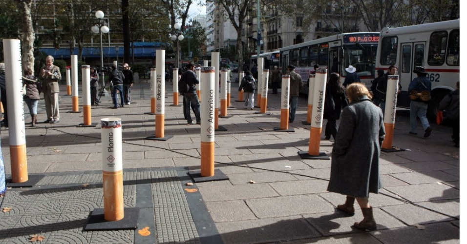 31.mai.2012 - Mulher caminha entre cigarros gigantes instalados na praça Cagancha, em Montevidéu, Uruguai, em homenagem ao Dia Mundial Sem Tabaco