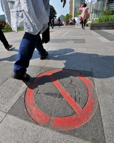 31.mai.2012 - Pedestre passa em calçada com aviso de que é proibido fumar no Dia Mundial sem Tabaco em Seul, na Coreia do Sul. O governador da cidade proibiu o fumo em praças, parques, ponto de ônibus e escolas