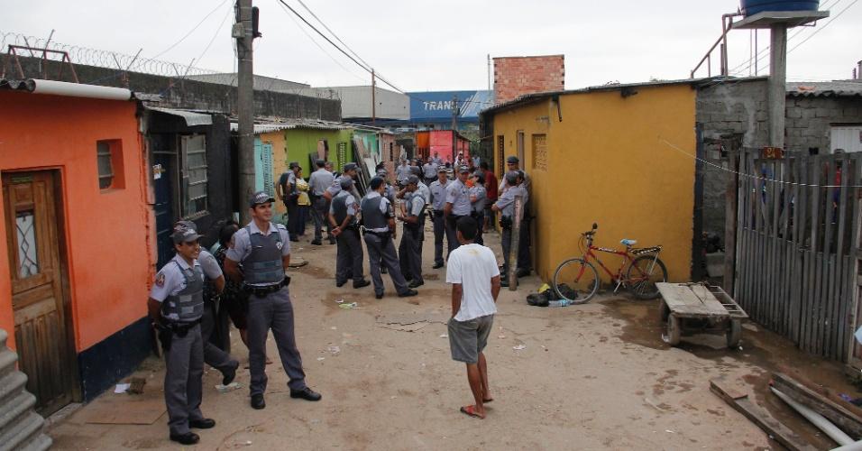 31.mai.2012 - Policiais observam movimentação em terreno no Jardim Cumbica, em Guarulhos, São Paulo. Cerca de 30 famílias devem ser retiradas do local durante reintegração de posse nesta quinta-feira (31)