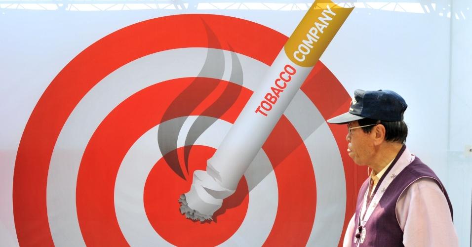 31.mai.2012 - Sul-coreano caminha e passa por pôster com mensagem anti-tabagismo quando diversos países estão realizando a campanha do Dia Mundial Sem Tabaco