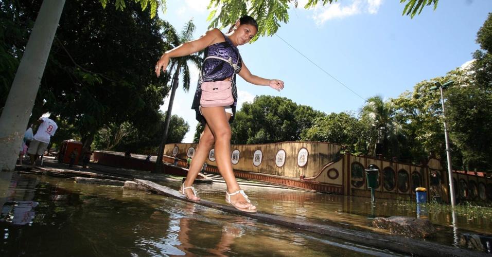 31.mai.2012 ? Mulher se equilibra para atravessar passagem alagada na região central de Manaus. O nível do rio Negro está em 29,78 metros, o mais alto dos últimos 110 anos. Várias cidades estão alagadas