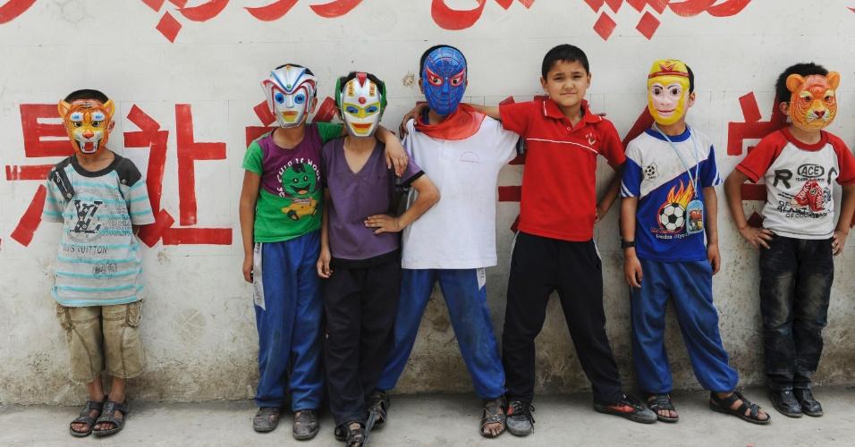 Estudantes de minoria étnica usam máscaras para tirar foto em frente a muro pintado com slogan educativo nas línguas chinesa e uigur em Asku, na região autônoma de Xinjiang Uighur