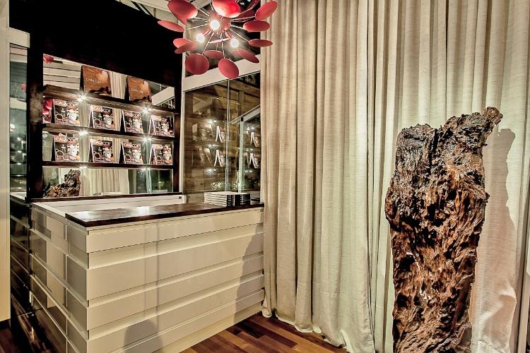 A arquiteta Gisela Ribeiro projetou dos 13m² da Bilheteria da Casa Cor PR usando vidro. Os móveis brancos  têm aplicações de espelhos e madeira
