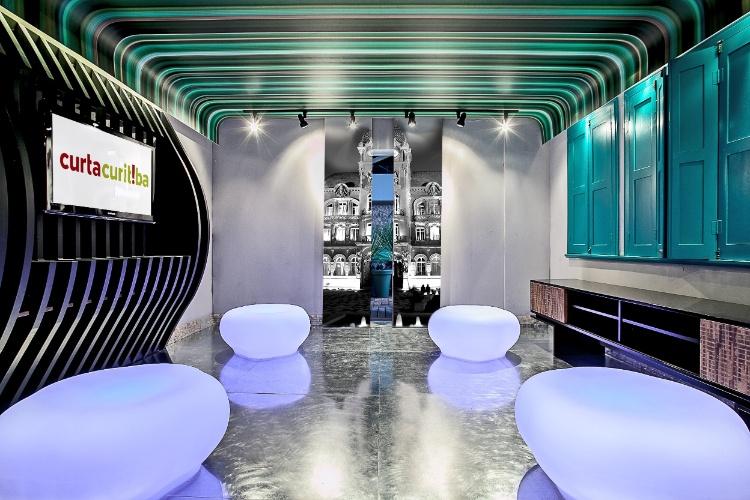 """A designer de ambientes Walkiria Nossol Lobo da Rosa e o designer Pedro Nossol assinam o Lounge Promocional """"Curta Curitiba"""". Desenvolvido a partir de técnicas sustentáveis, o espaço tem a intenção de divulgar os atrativos da cidade"""
