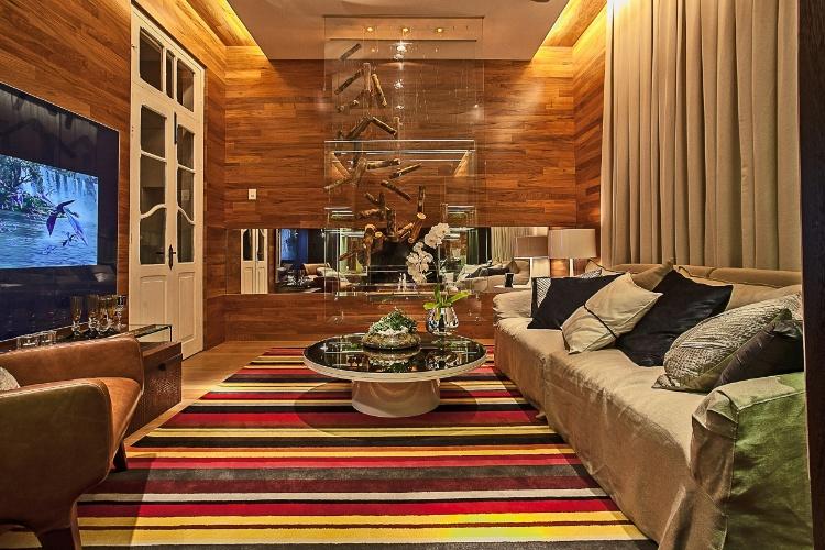Com 20m², a Sala da Lareira é assinada pela arquiteta Suzane Simon. O destaque do ambiente é a lareira a gás, suspensa e em vidro