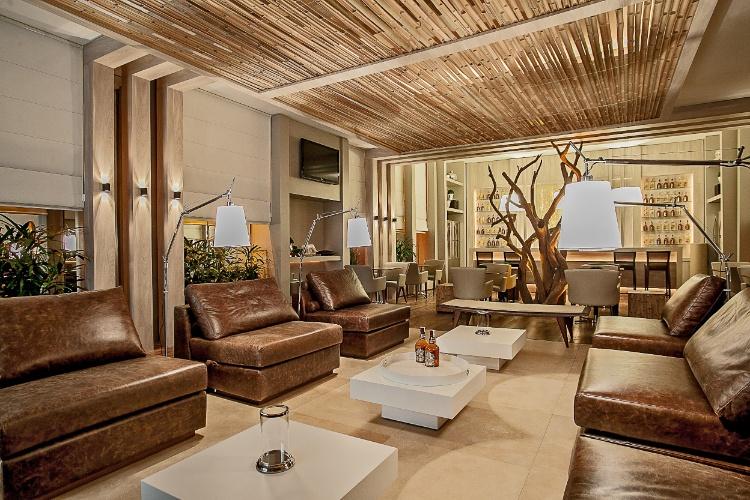 Lounge Bar pensado pelas arquitetas Caroline Andrusko e Eliza Schuchovski. O projeto evidencia materiais claros e de cores neutras em 120m²
