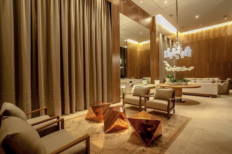 Lounge Simmetria, projetado pelo arquiteto e urbanista Jayme Bernardo para a 19ª Casa Cor Paraná. No ambiente, destaque para o lustre de cristais Baccarat e para as obras de Marcos Coelho Benjamim e Carlos Eduardo Zimmermann, combinados às cores neutras e às madeiras