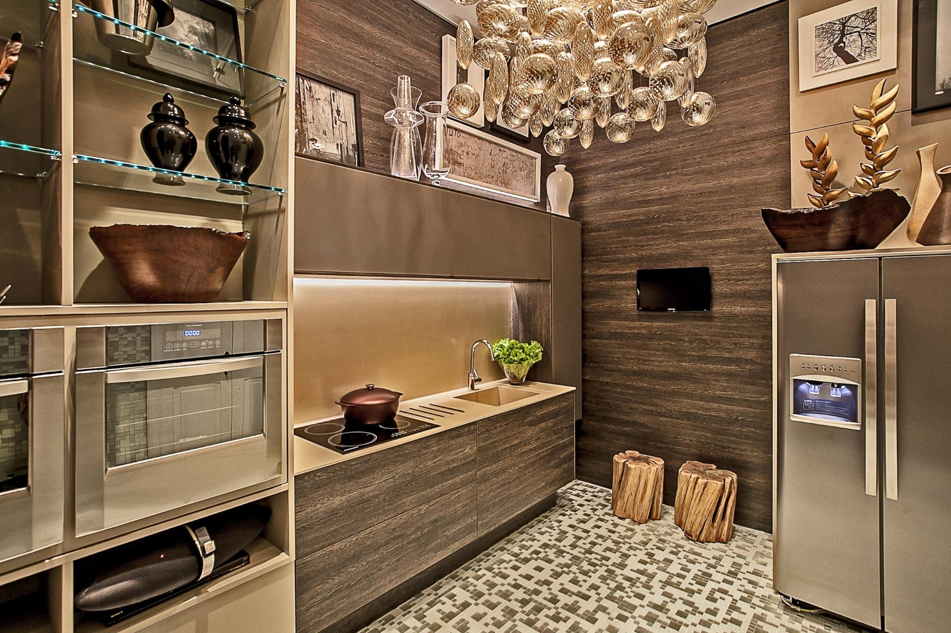 Os 22m²  da Cozinha e Lavanderia da Casa Cor PR foram criados pelo arquiteto Marcelo Lopes. No ambiente, destaque para o corin nos tampos, as pastilhas em parte das paredes e piso e os revestimentos amadeirados