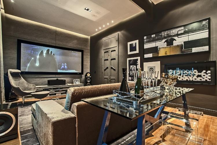 Os arquitetos Mauricio Pinheiro Lima e Carla Matiolli assinam o Home Theater - de 35m² - da Casa Cor PR. O projeto preservou vários elementos arquitetônicos e decorativos existentes no imóvel, como uma viga com detalhes arredondados e as janelas originais, além de pisos e rodapés
