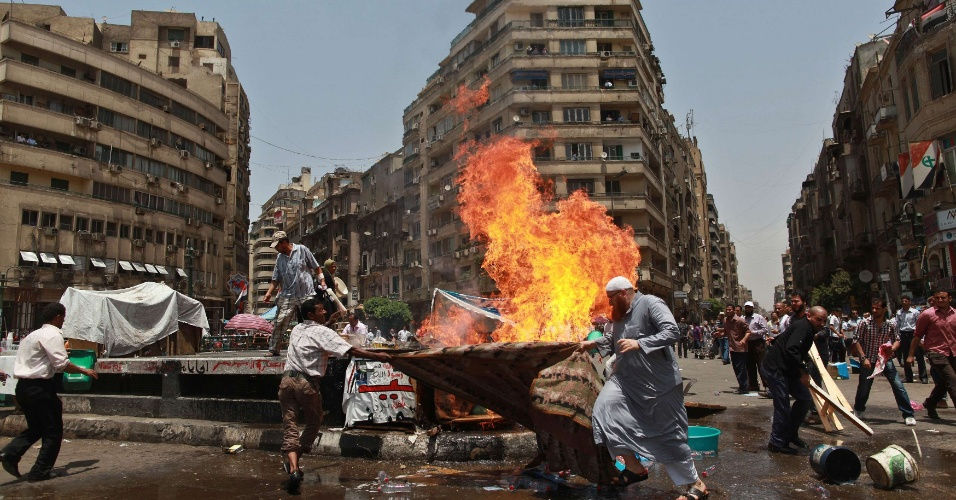 3.jun.2012 - Manifestantes tentam apagar inc&#234;ndio na pra&#231;a Tahrir, no Cairo, Egito, ap&#243;s botij&#227;o de g&#225;s explodir. Desde que o tribunal condenou o ex-presidente Hosni Mubarak &#224; pris&#227;o perp&#233;tua, os eg&#237;pcios ocupam o local para exigir que o ex-ditador seja condenado &#224; pena de morte
