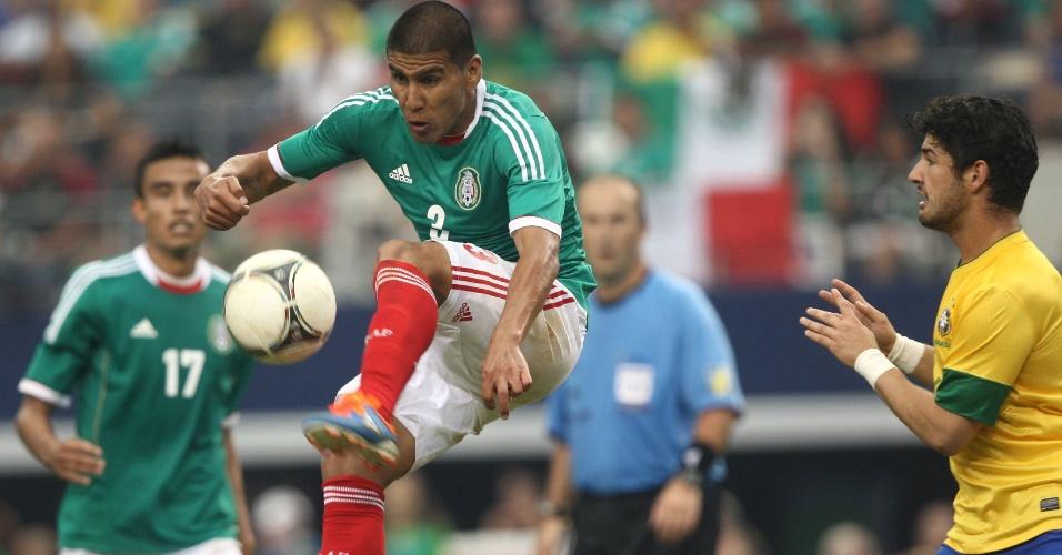 Alexandre Pato observa o jogador do México tentar afastar a bola