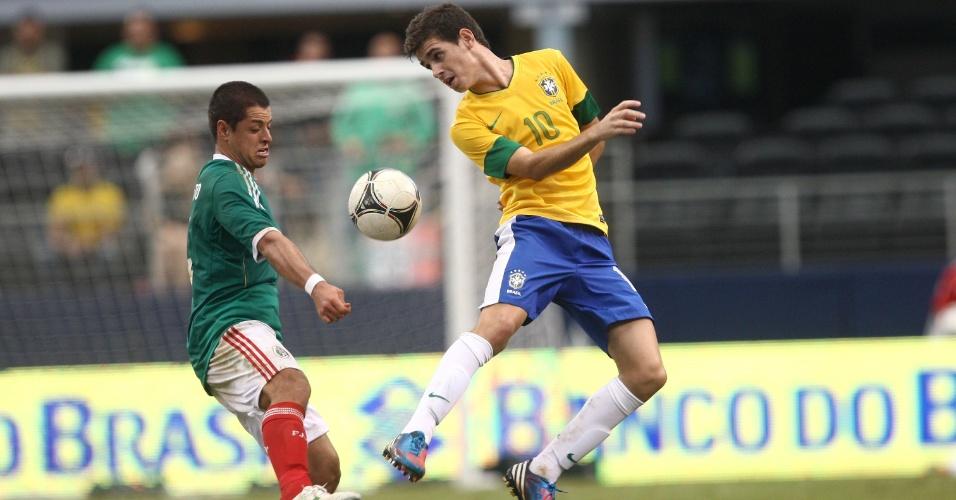 Oscar, meia da seleção brasileira, disputa a bola com o atacante Chicharito, do México