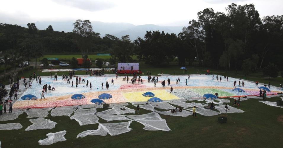 05.jun.2012 - Participantes usam seus pés para ajudar a pintar painel de 1.600 metros quadrados, em tentativa de colocar o feito no livro dos recordes, durante evento de caridade em Hong Kong, na China