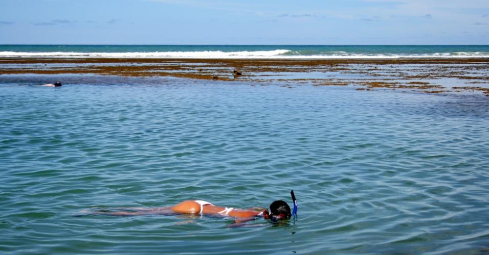 Mulher mergulha na Praia do Forte, na Bahia