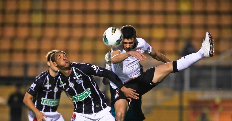 Alex, meia do Corinthians, briga no alto pela bola com jogador do Figueirense, durante duelo no Pacaembu