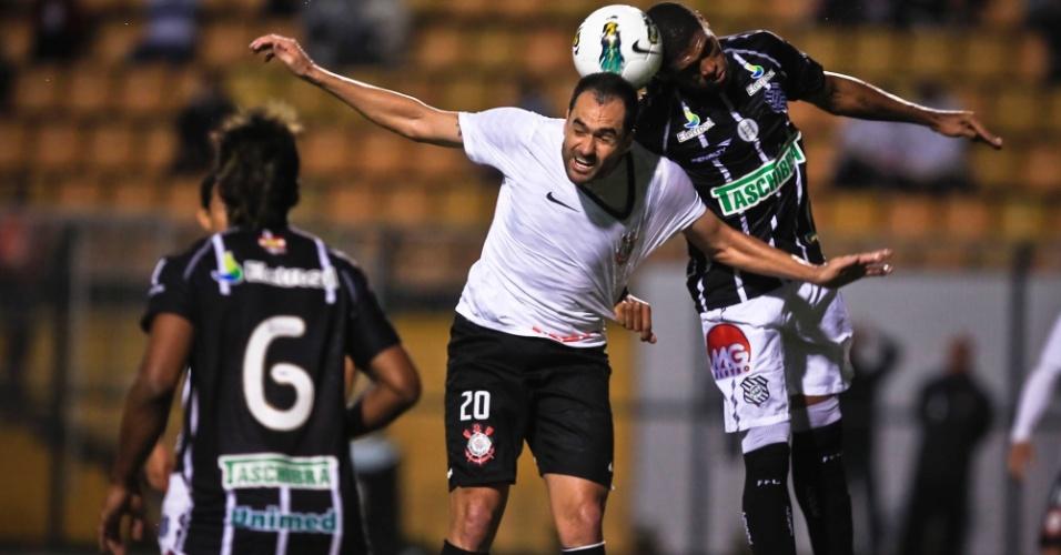 Danilo, meia do Corinthians, briga pela bola no alto contra jogador do Figueirense, em jogo no Pacaembu