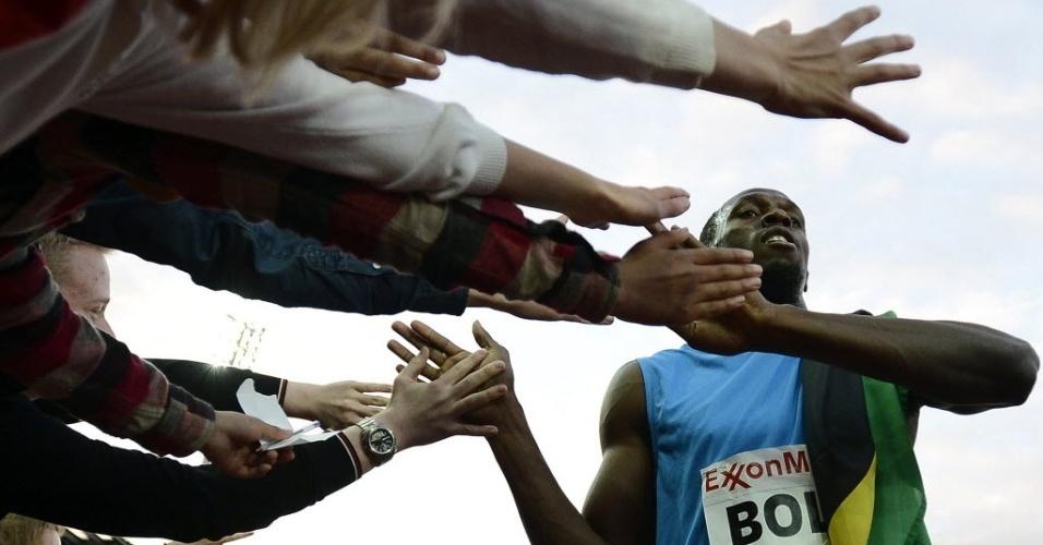 Usain Bolt, da Jamaica, celebra vitória dando a mão para o público na quinta etapa da Liga Diamante em Oslo, na Noruega