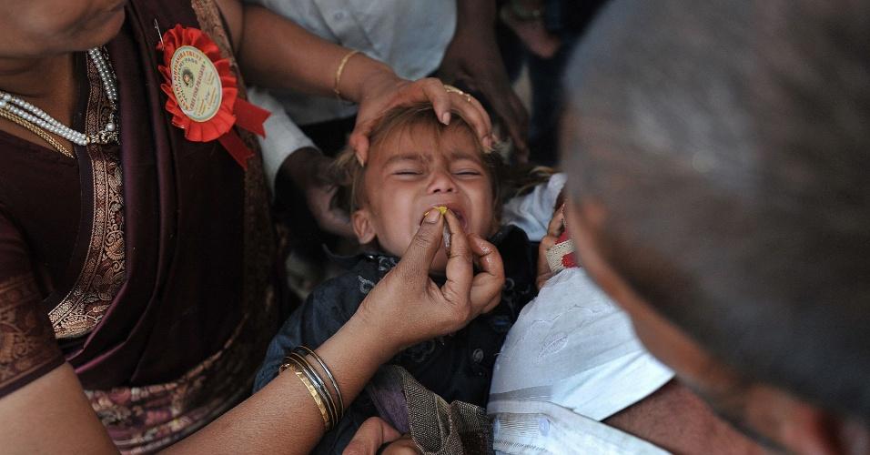 8.jun.2012 - Membro da família Batini administra medicamento tradicional a menino no estádio Katedan, em Hyderabad, na Índia