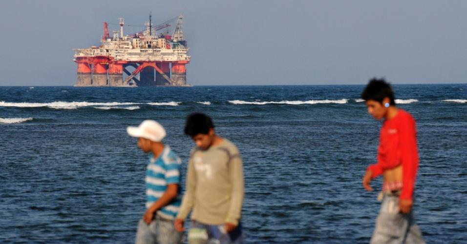 8.jun.2012 - Pessoas caminham na praia próximo a plataforma de perfuração de petróleo da estatal Pemex em Veracrus, no México