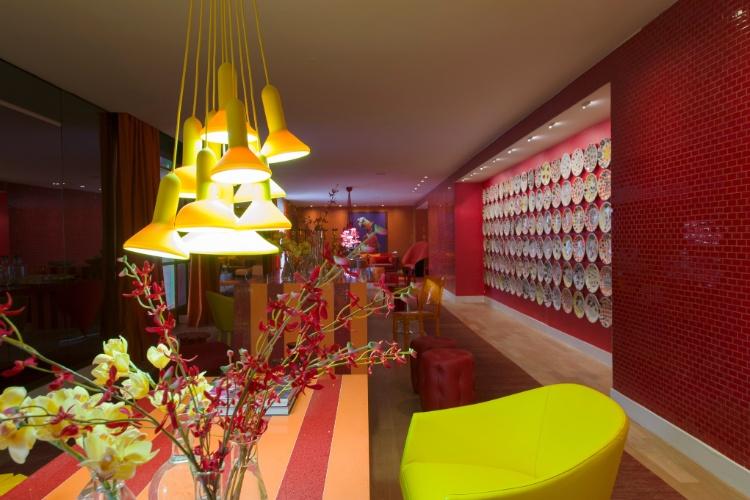 O mobiliário da alemã Kare e a iluminação da La Lampe ajudam a compor o cenário de cores intensas do Living assinado por Brunete Fraccaroli. O espaço homenageia a apresentadora Sabrina Sato. Destaque para a parede coberta por pratos estampados com caveiras e para o laranja que determina o tom da ambientação