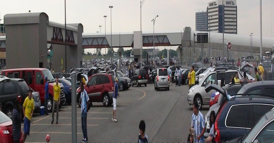 Torcedores jogam bola no estacionamento do estádio